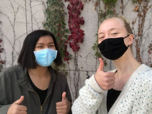 Two masked friends give a thumbs up