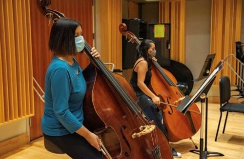 Two double bassists with music stands in a rehearsal.