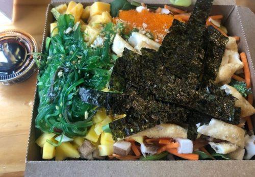 Colorful take-out food in a cardboard container.