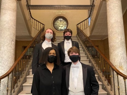 Four formally-dressed musicians wearing face-masks pose together on a marble staircase.