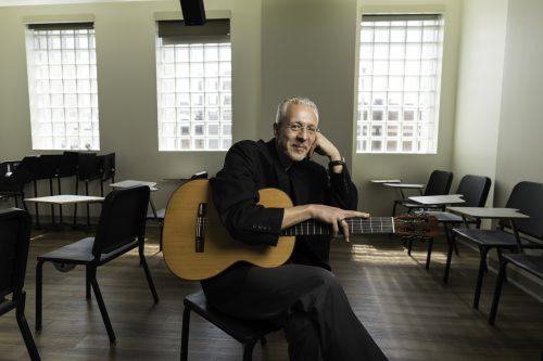 Petar Kodzas with guitar in classrroom photo