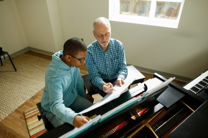A Piano teacher points out something in a musical score.