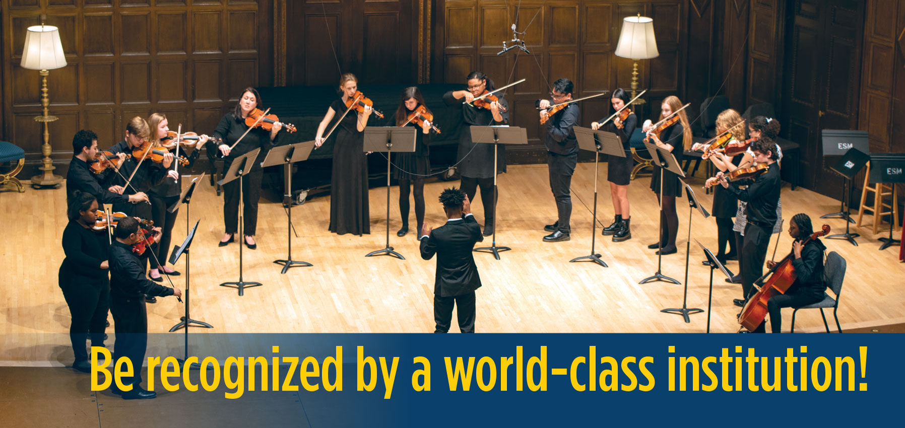 An ECMS Diploma student conducts a string ensemble of his peers on stage in a concert at Kilbourn Hall