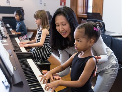 image of teacher with child at piano