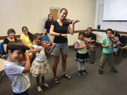 image of teacher with small children playing violins