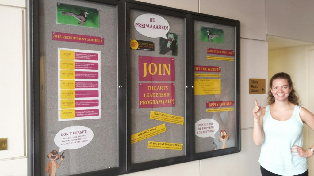 """Lisa Nickels, Summer Office Assistant, ALP: Putting up the ALP recruitment board outside of Sibley for fall 2015. Lisa and Blaire have been listening to Disney music on Pandora all summer, so Lisa was inspired to choose """"Be Prepared"""" as the board's theme!"""