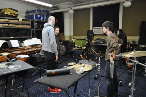Composer Jonathan Pfeffer (grey hoodie) guides the members of Third Coast Percussion through a series of musical ideas. Ensemble members from left to right: Robert Dillon, David Skidmore, Peter Martin (kneeling), and Sean Connors.