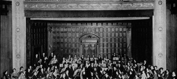 A 70-member orchestra poses with instruments on stage in Kilbourn Hall.