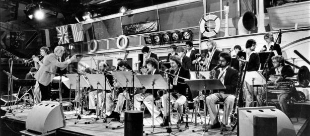 Ray Wright conducts the Eastman Jazz Ensemble during a performance, with scenery depicting a cruise ship in the background.