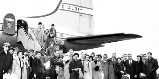 Members of the Eastman Philharmonia gather for a photo in front of the tail section of a Hermes IV airplane after deplaning.Members of the Eastman Philharmonia gather for a photo in front of the tail section of a Hermes IV airplane after deplaning.