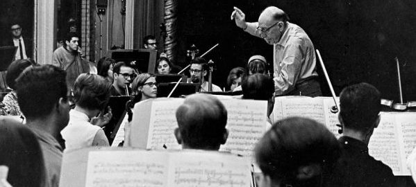 Igor Stravinsky conducts a student orchestra on the Eastman Theatre stage, viewed from the 3rd row of the 2nd violin section.