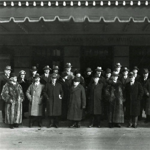 Black and white photo of 22 people, wearing winter coats, standing under the awning outside of the Eastman School of Music's main entrance.