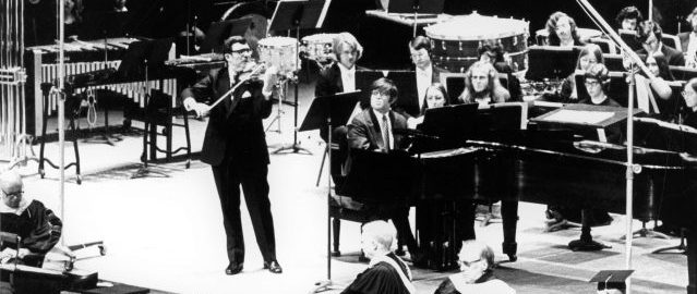 Zvi Zeitlin and Robert Freeman perform at Mr. Freeman's inauguration in the Eastman Theatre (1973). Photograph from ESPA 37/18A. Zvi Zeitlin, violin, and Robert Freeman, piano, perform on the Eastman Theatre stage, with a student ensemble seated in the background.
