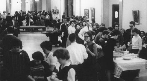 Several dozen students mingle during a reception in Cominsky Promenade.