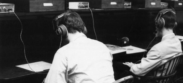 Two students wearing headphones seated at listening stations in the old Sibley Music Library (circa 1970s).