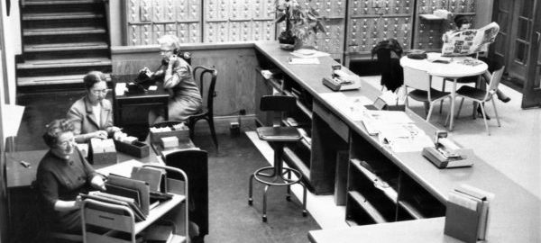 Candid, birds-eye view of the front desk of the old Sibley Music Library, showing Ruth Watanabe and two librarians at work.