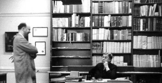 A man in a trench coat stands near Barbara Duncan, seated in her office in front of three full bookshelves.