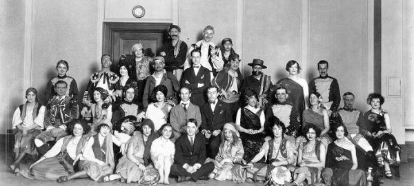 32 students, wearing costumes for the opera Carmen, pose as a group with four men wearing suits and ties.