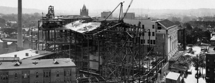 Black and white photo of the construction of Eastman Theatre, showing the building's steel structure as viewed from the roof of the YMCA building on Gibbs Street.