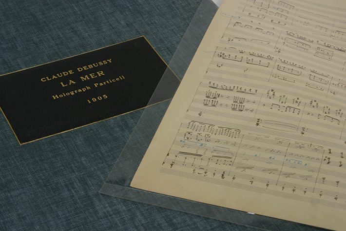 """One page from Debussy's holograph short score to """"La Mer"""" displayed with the manuscript's protective case."""