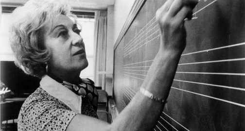 """The Marian McPartland Collection includes a large series of photographs from McPartland's professional career. This photograph, taken by Louis Ouzer during one of Marian McPartland's visits to Eastman, depicts McPartland """"trying to write a blues."""" [Marian McPartland Collection, Box 28, Folder 2, Sleeve 14]"""