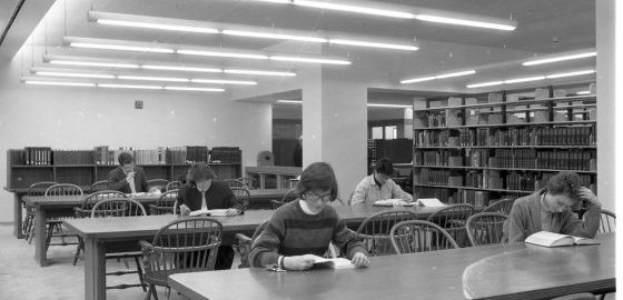 Black and white photo of the second-floor reading room in the new Sibley Music Library, showing five students studying at long tables.