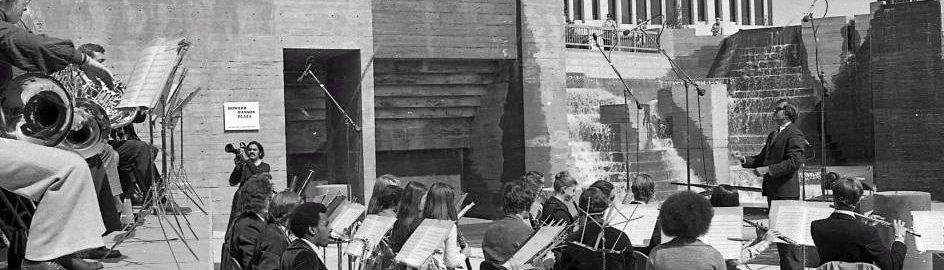 Robert Freeman conducts wind ensemble of Eastman students on a stage in a sunken, concrete plaza.