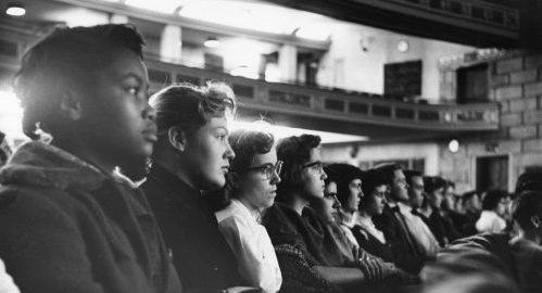 A row of young students seated in the audience of Eastman Theatre.
