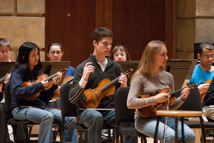 String players in the Eastman Chamber Orchestra practice a new technique for performing baroque music.
