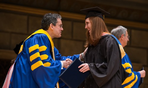 Eastman Students' Association President Molly  O'Roark shakes hands with ESM dean Doug Lowry. // University of Rochester Eastman School of Music commencement  ceremony in Kodak Hall at Eastman Theatre May 19, 2013. // photo by J. Adam Fenster / University of Rochester