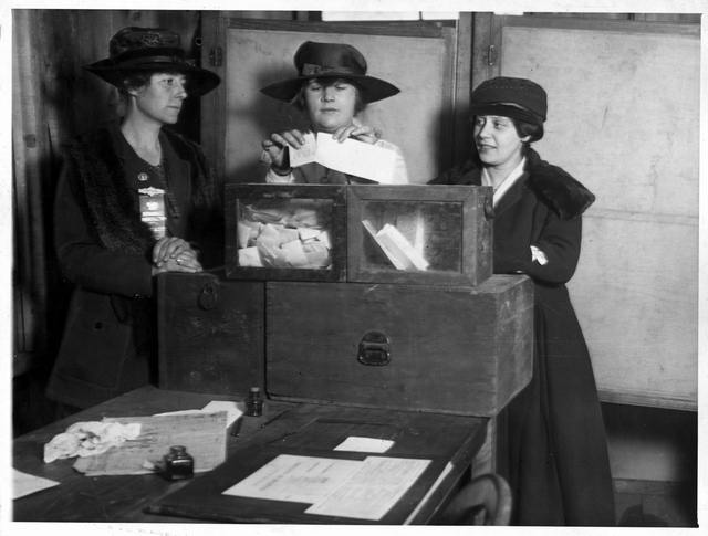 Three suffragettes standing around a tabletop ballot box casting their votes